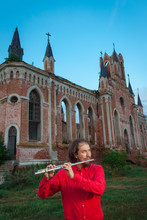 Musician In Red Playing The Flute Near An Old Castle In The Evening