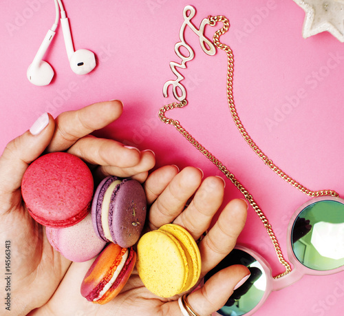 woman hands holding macaroons with lot of girl stuff on pink