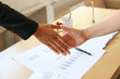two business persons hand shake with sale report charts paper blur background