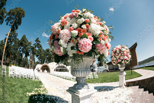 Fotografía  Beautiful wedding ceremony design decoration elements with fresh flowers composition, floral design, petals roses and chairs