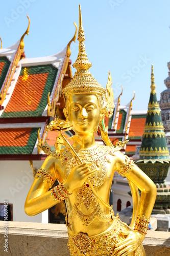 Golden Kinnaree statue against pagoda background on display at wat pra kaew in Bangkok, Thailand Poster