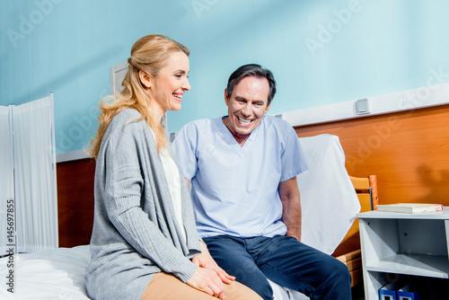 Fototapeta laughing wife visiting elderly husband in hospital obraz na płótnie