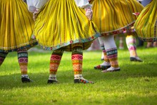 Traditional Dancers Dancing On The Grass With Colourful Pattern Design Native Shoes And Dresses. Folk Dance.