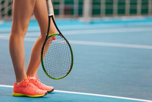 Legs Of Young Girl In A Closed Tennis Court With Racket