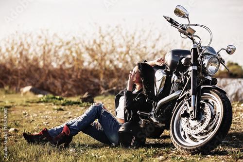 piekna-brunetka-siedzaca-na-ziemi-oparta-o-motocykl