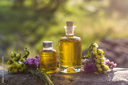 Fotografie, Obraz  bottles with natural aroma oil over nature background.