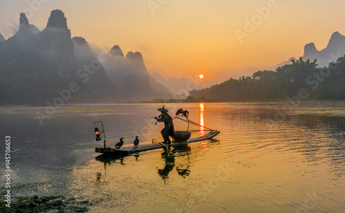 Staande foto Guilin Cormorant fisherman stands on the ancient bamboo boat with lamp and birds in the sunrise - The Li River, Xingping, China