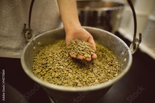 Papiers peints Salle de cafe barista holding bucket full of green coffee beans