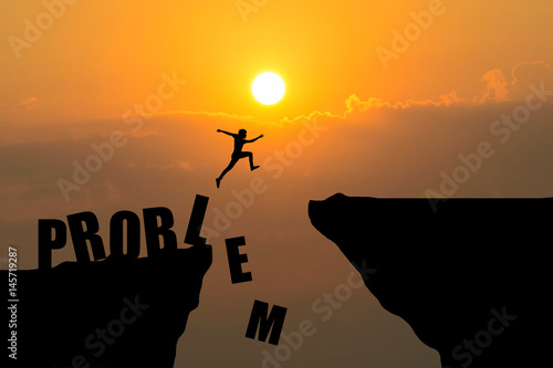 Man jumping over Problem text over cliff on sunset background,Business concept i Wallpaper Mural