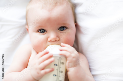Photo  Pretty baby girl drinks water from bottle lying on bed