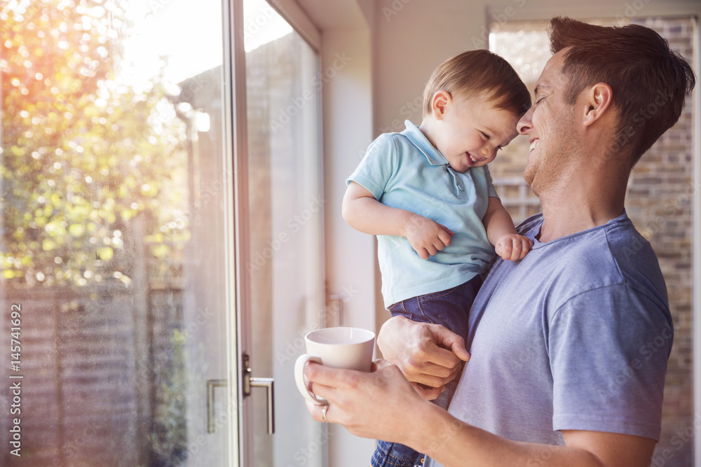 Fototapeta Father holds toddler son while drinking coffee at home, by the window