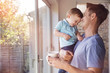 canvas print picture - Father holds toddler son while drinking coffee at home, by the window