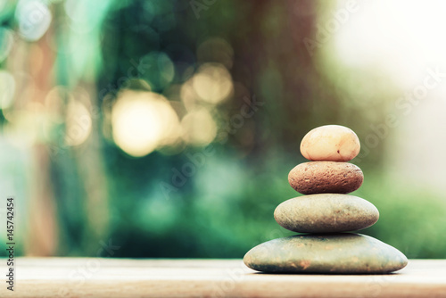 Carta da parati  Stack of zen stones on ground with blurred nature background.