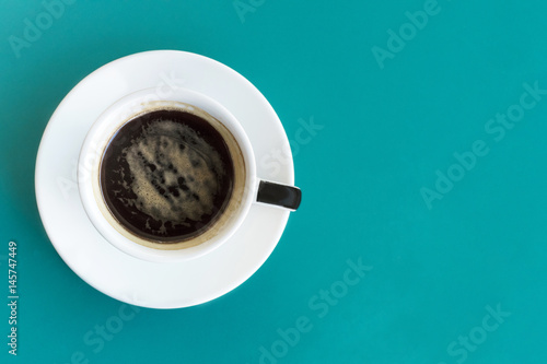 Cup of coffee, shot from above on vibrant turquoise