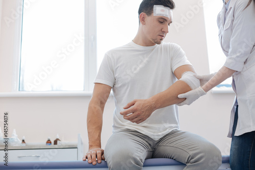 Fotografie, Obraz  Cheerless wounded man looking at his injury