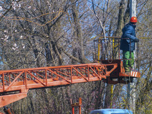 Worker On Loong Machine Lift At An Electric Pole