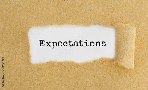 Text Expectations appearing behind ripped brown paper. Tableau sur Toile
