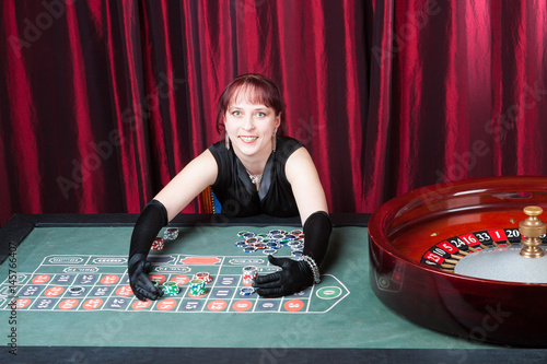 Plakat  young woman wearing  black gloves and black dress wins in a casino