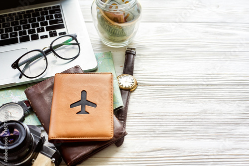 Obraz na płótnie travel and wanderlust concept, planning summer vacation, space for text jar with money map compass photo camera glasses wallet watch laptop on white wooden background time to travel