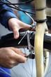 Hamulce rowerowe, regulacja klocków. Mężczyzna wymienia klocki hamulcowe w rowerze