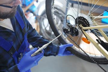 Sezon rowerowy, czyszczenie roweru. Mechanik w serwisie rowerowym czyści rower sprężonym powietrzem.