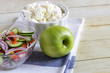 Foods for healthy eating: cottage chesse, apple, salad on light wood background