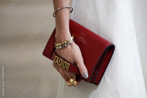 c83025ebd610 A guest holds a handbag as she arrives to attend the French fashion house  Christian Dior Fall Winter 2017-2018 women s ready-to-wear collection  during ...