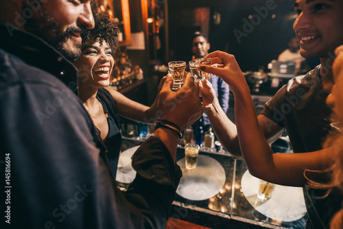 Fotografia Friends toasting each other with shots of vodka