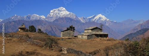 Staande foto Nepal Autumn day in the Himalayas. Seventh highest mountain of the world, Dhaulagiri. Old stone house and shed.