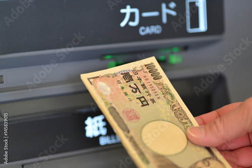 Fototapeta a woman's hand withdrawing money at ATM obraz