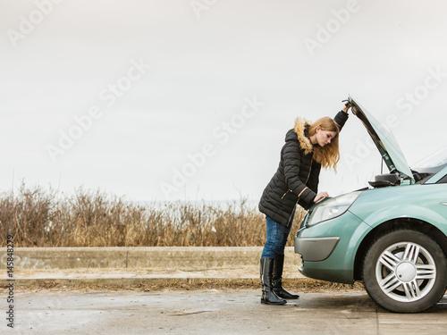 Blonde woman and broken down car on road Fotobehang