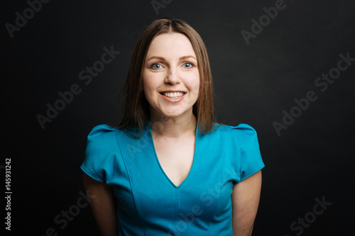 Fotografia  Cheerful young woman smiling in the black colored studio