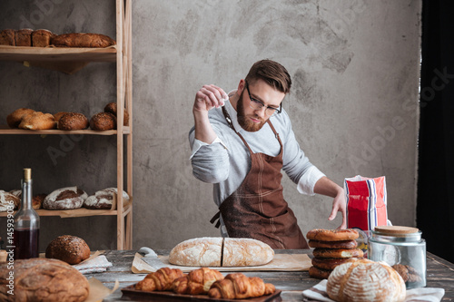 Fototapeta Concentrated man baker standing at bakery near bread