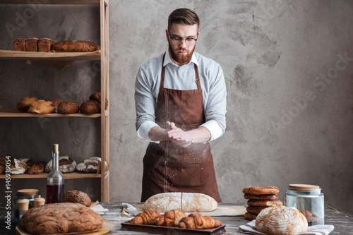 Fotografia Young concentrated bearded man wearing glasses baker