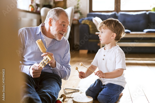 Grandfather and grandson playing music at home плакат