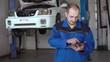 30s car mechanic in blue uniform using tablet in car repair auto service