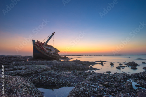 Foto op Aluminium Strand Fishing boat aground on the rocks for a long time at sea erosion disintegrated until only half a body which remains beautiful during twilight.