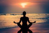Fototapeta Fototapety z morzem do Twojej sypialni - Kobieta ćwicząca jogę przy zachodzie słońca