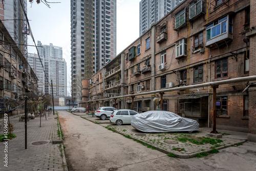 Une allée entre deux vieux immeubles de la ville de Xi'an et des buildings modernes en fond et des voitures garées