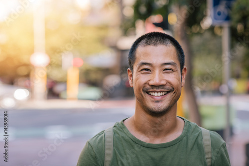 obraz PCV Young Asian man smiling confidently on a city street