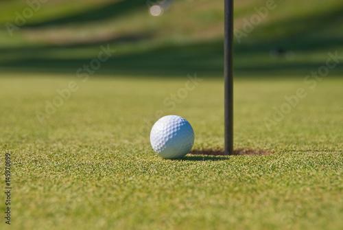 Fotografie, Obraz  Golf ball on green with flag.