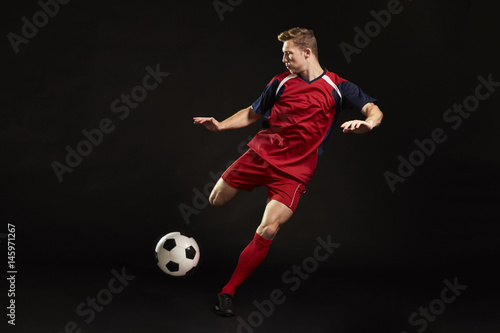 Valokuva  Professional Soccer Player Shooting At Goal In Studio
