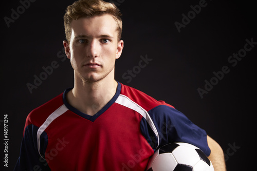 Fotografie, Tablou  Portrait Of Professional Soccer Player With Ball In Studio