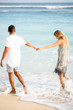 Couple Holding Hands and Strolling on Summer Beach