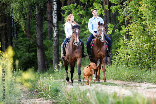 Young happy couple enjoying horse ride in a summer forest.