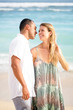 Smiling Couple Walking and Kissing on Beach