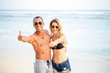 Happy young couple showing thumbs up on beach