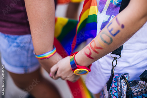 Fotografía  Close up of couple holding hands during pride parade