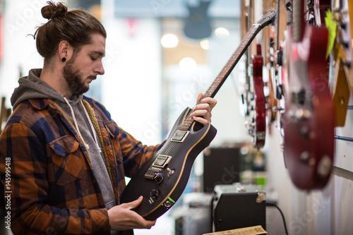 Spoed Foto op Canvas Muziekwinkel Young adult male looking at guitar in shop