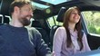Happy couple in love looking at each other showing joy driving car
